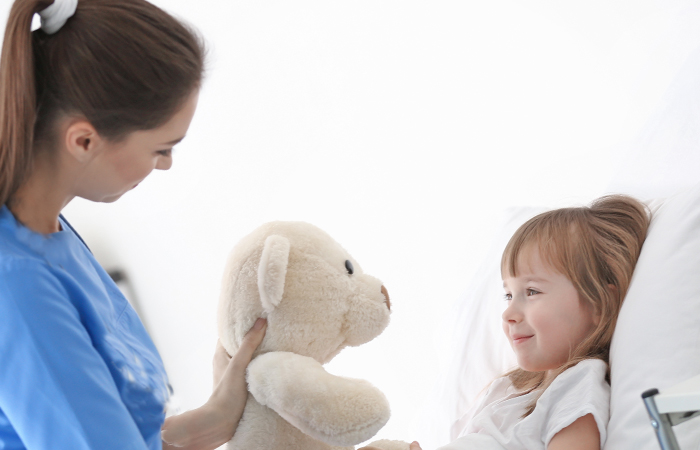 Sacred Heart Frequently Asked Questions page_nurse holding teddy bear to smiling little girl